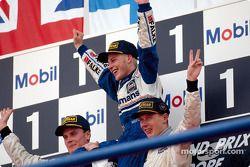 El podio: El Campeón Mundial Jacques Villeneuve con David Coulthard y Mika Hakkinen