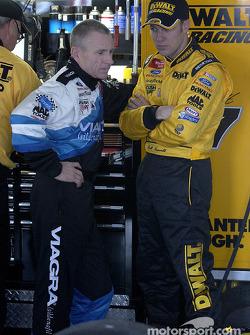 Mark Martin y su compañero de equipo Matt Kenseth platican en el área de garages