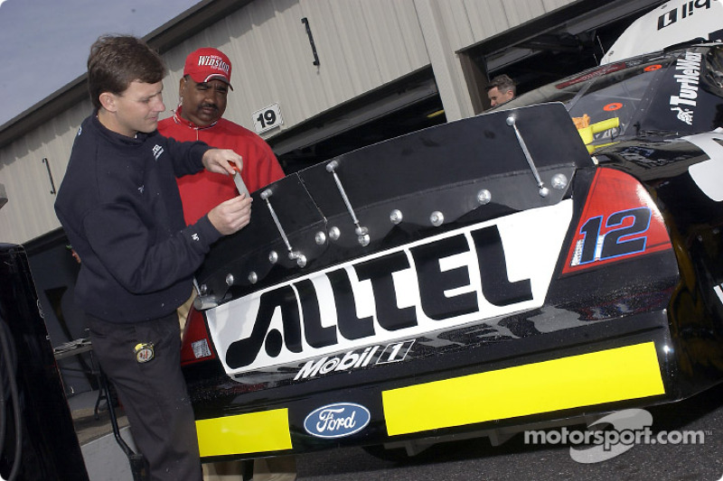 Un miembro de equipo viaja en el spoiler traser del Alltel Ford Taurus de Ryan Newman