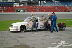 Jerry Hill aide don équipe à pousser le véhicule dans la pitlane