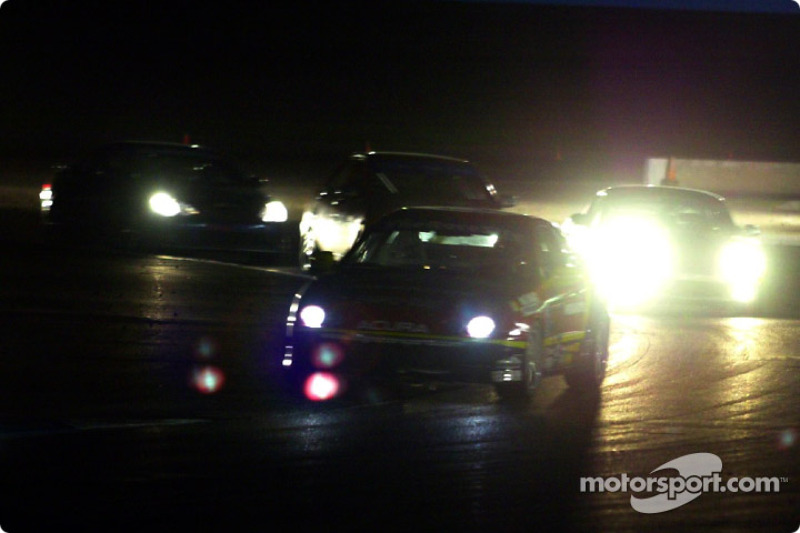 Several cars jockey for position in the dark during the UnitedAuto Touring 250
