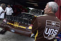 Dale Jarrett de pie mientras el equipo UPS trabaja en la parte trasera del auto luego de que Jarrett