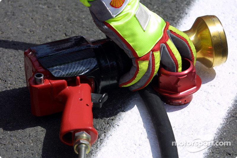 Gloved hand and tire changing gun
