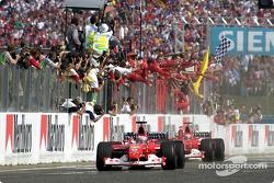 Rubens Barrichello passe le drapeau à damier devant Michael Schumacher