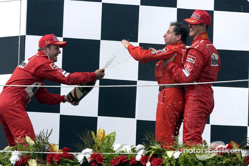 The podium: champagne for race winner Rubens Barrichello, Michael Schumacher and Jean Todt