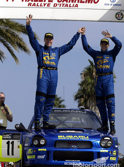 Petter Solberg and co-driver Phil Mills celebrate 3rd place podium