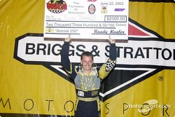Animal 250 race winner Kerry Parnell on the podium with his check