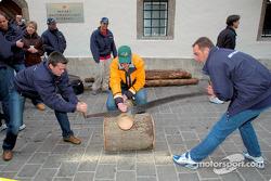 Los pilotos de BMW, Dirk Muller y Jorg Muller intentan aserrar un árbol