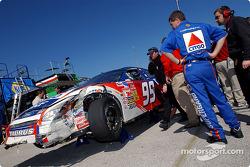 Paul Andrews, jefe de equipo del Citgo Ford Taurus evalua el daño del auto luego de que el piloto Je