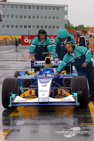 Sauber team members push the car