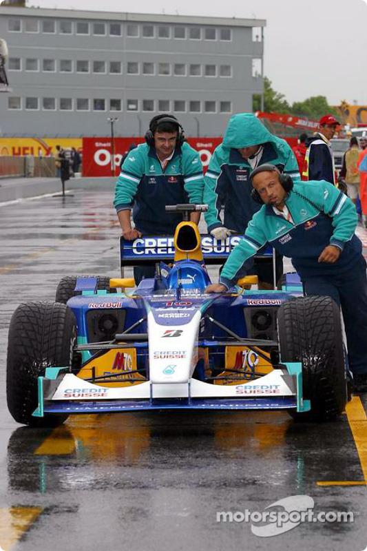 Los miembros del equipo Sauber empujan el coche