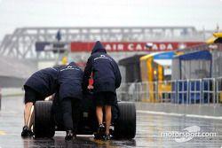Williams team members push the car on pitlane