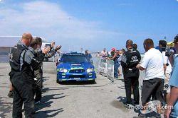 Rally winner Petter Solberg applauded by Hyundai crew members