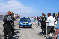 Rally winner Petter Solberg applauded by Hyundai crew members