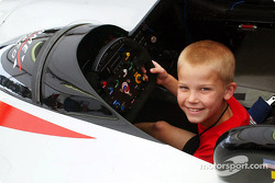 A young fan sits in a Panoz LMP01 Prototype during the Open House autograph party