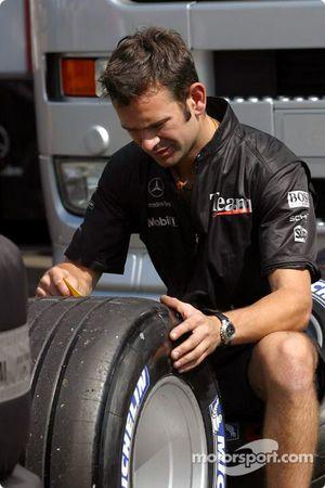 Un membre de l'équipe McLaren prépare les pneus