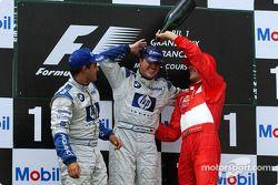 The podium: champagne for race winner Ralf Schumacher, Juan Pablo Montoya and Michael Schumacher