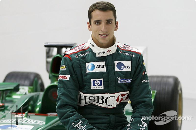 Justin Wilson poses with the Jaguar F1 car after his transfer to Jaguar Racing from Minardi at the J