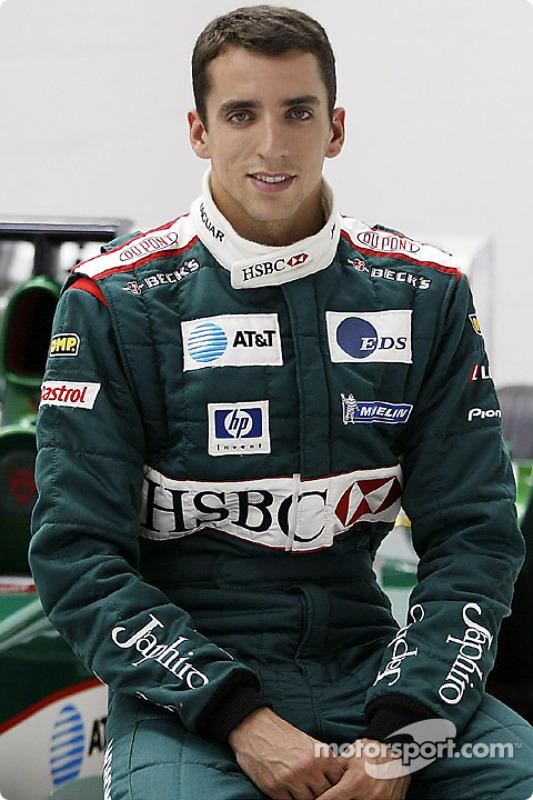 Justin Wilson posa con el coche Jaguar F1 después de su traslado a Jaguar Racing de Minardi en la fábrica de Jaguar Racing en Milton Keynes