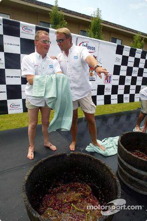 Comme ils se nettoient après le concours d'écrasement de raisin, les coéquipiers d'ADT Champion Racing Johnny Herbert et JJ Lehto comparent leurs notes; Herbert a remporté le concours