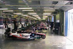 Huit Minardi F1 biplaces et deux Minardi F1 alignées dans le garage