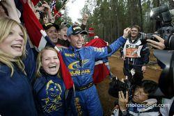 Petter Solberg célèbre sa victoire avec des fans au contrôle de la dernière spéciale