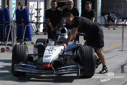 McLaren team members push car on pitlane