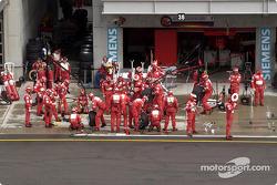 Los miembros del equipo Ferrari preparan área de pits