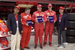 Jean Todt, Rubens Barrichello y Michael Schumacher recibe un regalo de Olympus