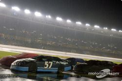Cars sit covered up under the rain on pit road