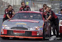 Les mécaniciens Roush Racing poussent la voiture de Kurt Busch