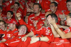 Michael Schumacher and Rubens Barrichello celebrate with Ferrari team members