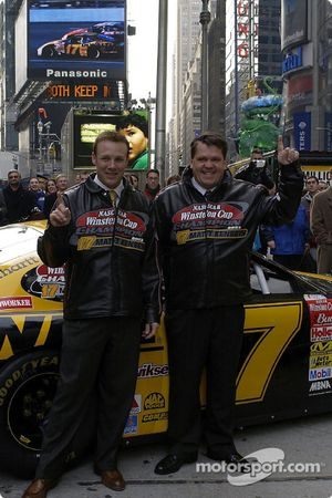 Matt Kenseth and Robbie Reiser pose in front of the big Panasonic screen in background playing a tribute video
