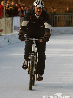 Dr Mario Theissen rides a bicycle on ice