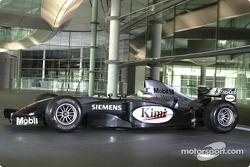 Une Formule 1 de l'équipe McLaren Mercedes devant la facade du McLaren Technology Centre