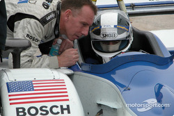 Dyson Racing driver Andy Wallace leans in to talk to James Weaver, who is seated in the car