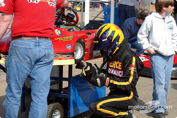 Jody Pierce in the driving suit and helmet takes a tire temperature check after a practice session
