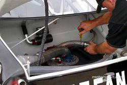 Un mécanicien ajuste les conduites d'essence dans le coffre
