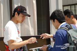 Tora Takagi signe des autographes