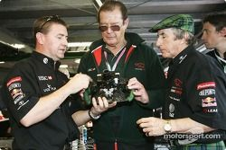 Jackie Stewart gives Roger Moore a guided tour of Jaguar pit area