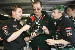 Jackie Stewart da a Roger Moore una visita guiada de la zona de boxes de Jaguar