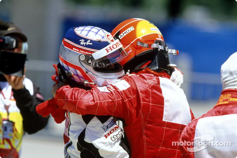 Takuma Sato and Michael Schumacher celebrate