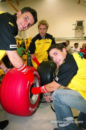 Timo Glock, Giorgio Pantano y Nick Heidfeld cambiar un neumático de Bridgestone rojizo y use un calc