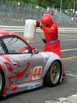 Un mécanicien du Flying Lizard Motorsports remet de l'essence dans leur Porsche GT3 RSR n°44