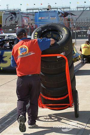Un membre du Tide Racing transporte un nouveau train de pneus vers les stands