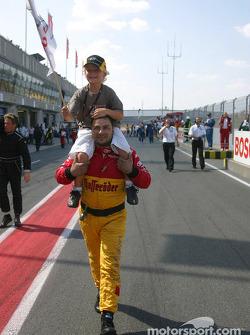 An Audi mechanic takes Tom Kristensen's son Oliver to the podium