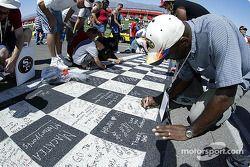 Fans autograph the start/finish line