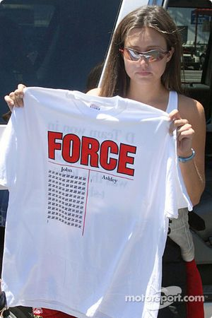 Ashley Force with a tee-shirt showing her wins and her dad's wins