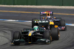 Heikki Kovalainen, Lotus F1 Team leads Sebastian Vettel, Red Bull Racing