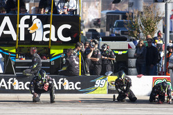 The Aflac crew clean debris off pit road after oil was spilled